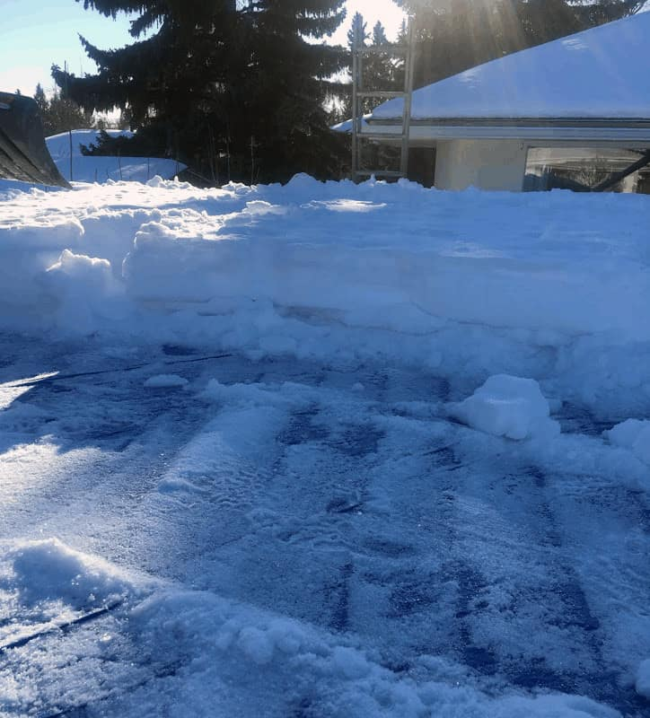 A flat roof with snow being removed