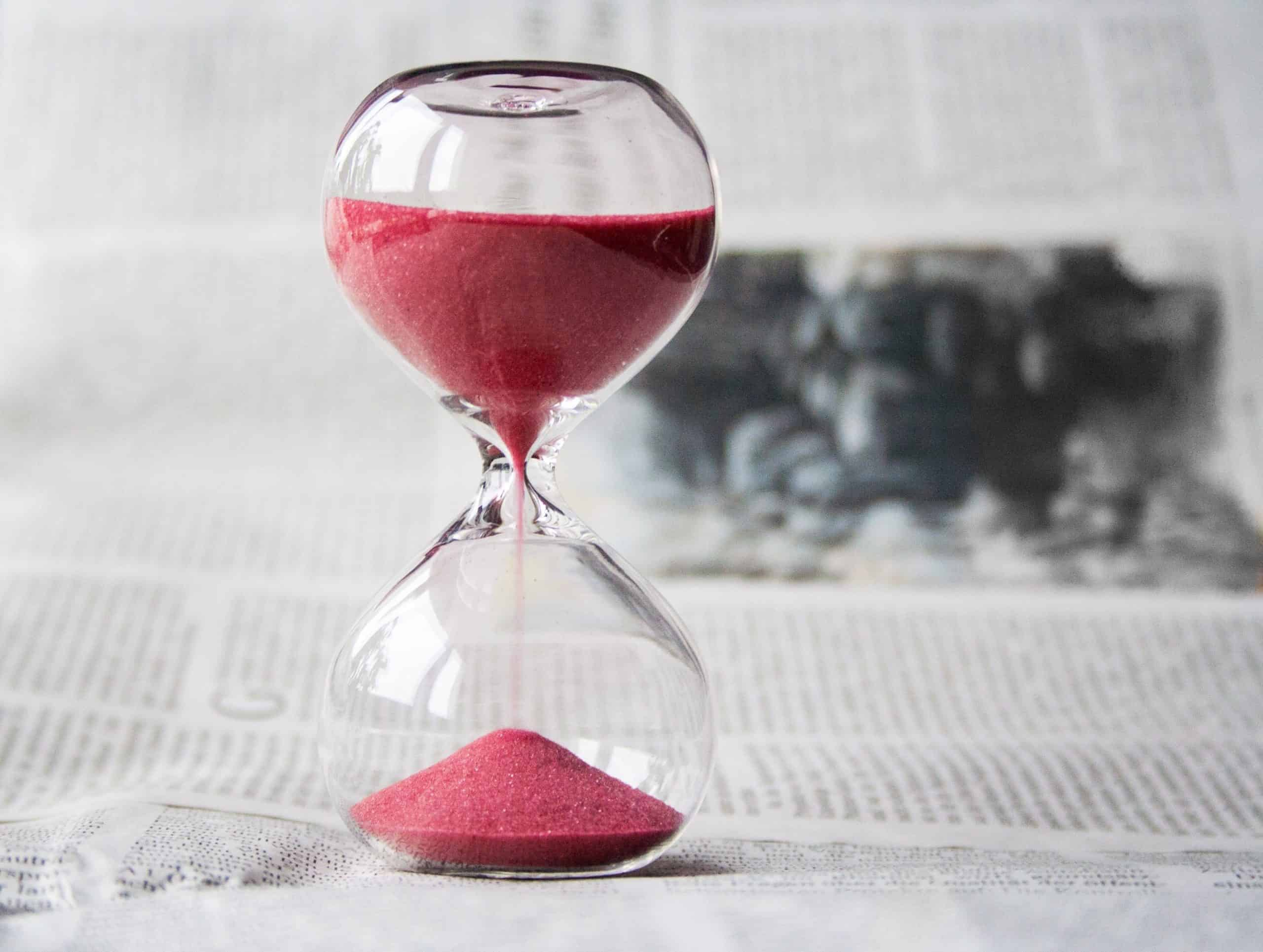 A hourglass timer on a table ontop of a newspaper