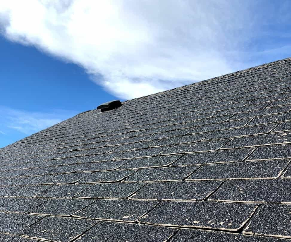 Picture of a roof with worn out shingles needing repair with the sky in the background