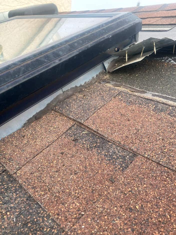 Nail being lifted from roof damage around the flashing on a skylight