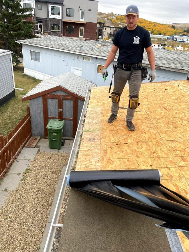 Roofer applying underlay on a new roof in calgary
